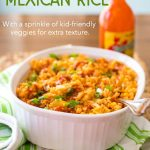 Homemade Mexican Rice in a white baking dish with hot sauce in the background.