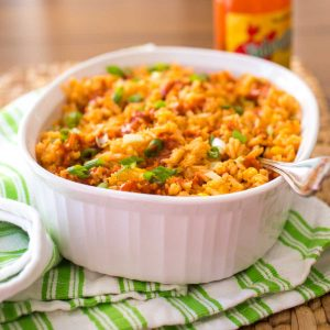 A white baking dish is filled with baked Mexican Rice. The tomato sauce base gave the rice a yellow-orange color. Hot sauce is drizzled over the top and fresh green onions are sprinkled for garnish.