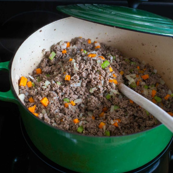 A big green pot holds browned ground beef with chopped carrots, onions, and celery to be portioned for the freezer.