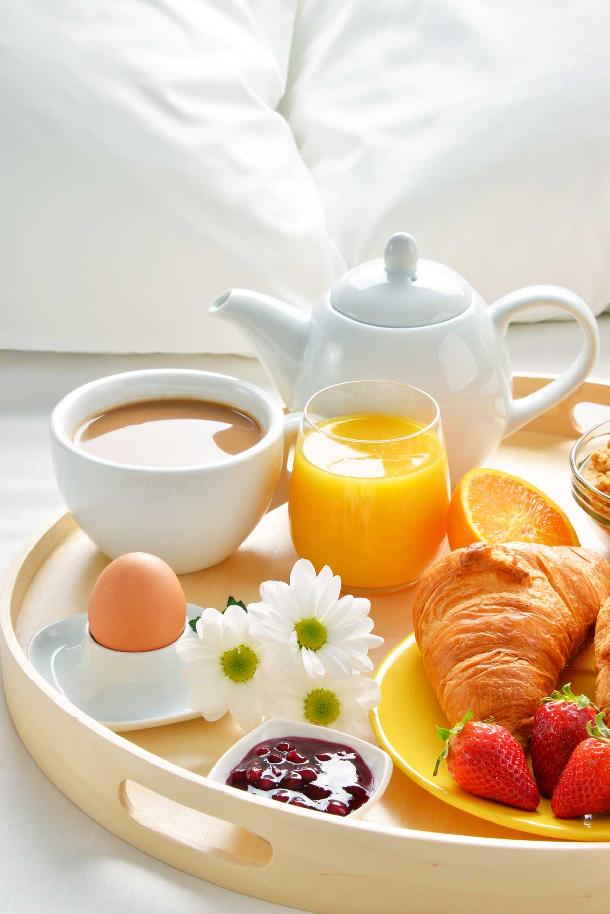 A breakfast tray sits on a bed with white pillows. There's a tea pot, coffee, orange juice, and a croissant with fresh fruit.