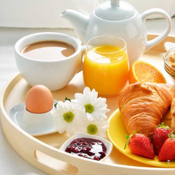 A round tray holds a white tea pot, a coffee cup with milky coffee, 3 fresh daisies, a brown egg, and a yellow plate with a croissant and fresh strawberries with a tiny cup of jam.