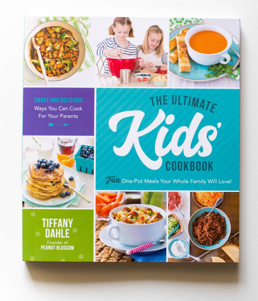 A copy of The Ultimate Kids' Cookbook by Tiffany Dahle sits on a table.