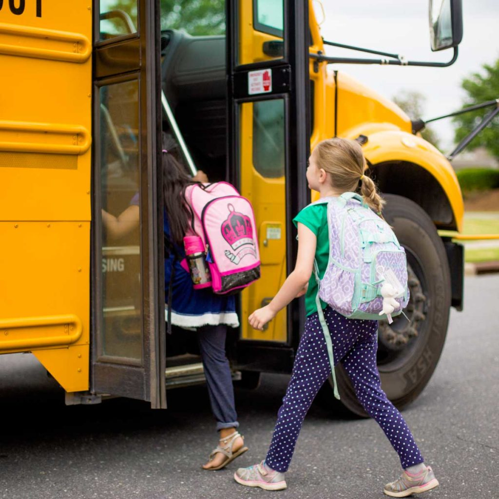 A young girl gets on a yellow school bus on the first day of school.