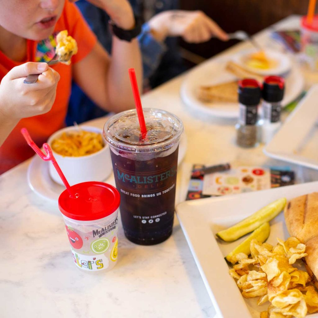 Restaurant cups and entrees on a table with a family eating a meal.