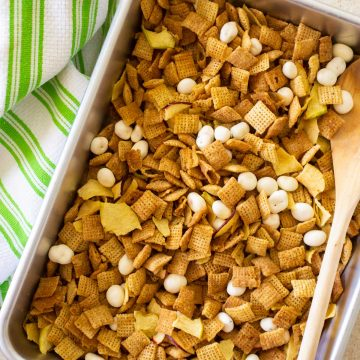 A pan of apple pie chex mix has yogurt covered raisins mixed in with a wooden spoon next to a green striped towel.