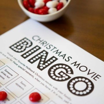 Christmas movie bingo game has red candy markers holding place.