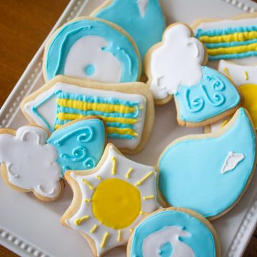 A platter of sugar cookies features weather-related shapes. Sunshine, Rain Drops, Cloud and Wind.
