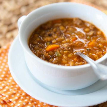 A bowl of sausage lentil soup sits on an orange napkin with a spoon ready for eating.