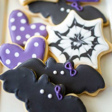 Sugar cookie platter with black bat sugar cookies with purple polka dot hearts and spider web shapes.