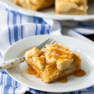 A square of crumble apple pie bar has a drizzle of caramel over the top and a fork to the side.