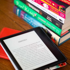 A Kindle reader sits on a table next to a stack of books.