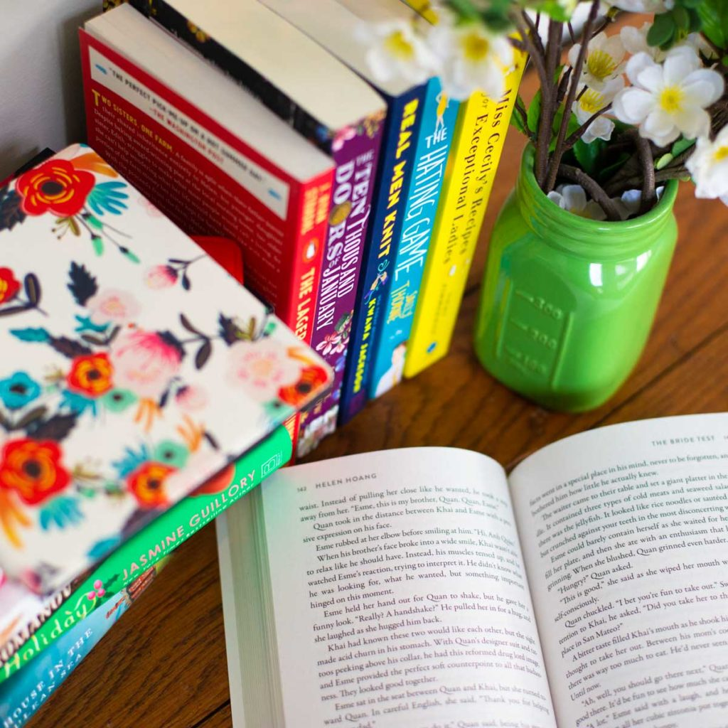 A book is open on a table next to stacks of other books and a flower vase.