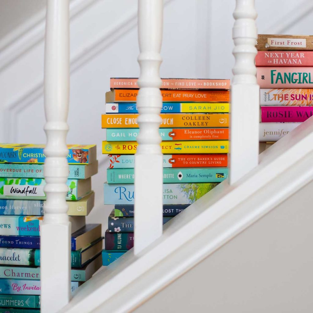 Piles of book club books sit on a set of stairs