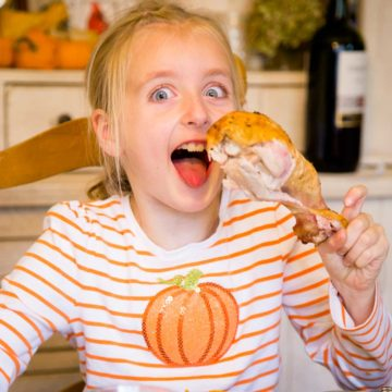 A young girl holds a giant turkey leg at the Thanksgiving table.