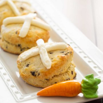 A platter of hot cross biscuits has a ceramic carrot accessory. Each biscuit has a cream cheese frosting cross on the top and currants inside.