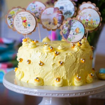 Adorable yellow Winnie the Pooh cake features tiny bees and several Pooh-themed cake picks on top.