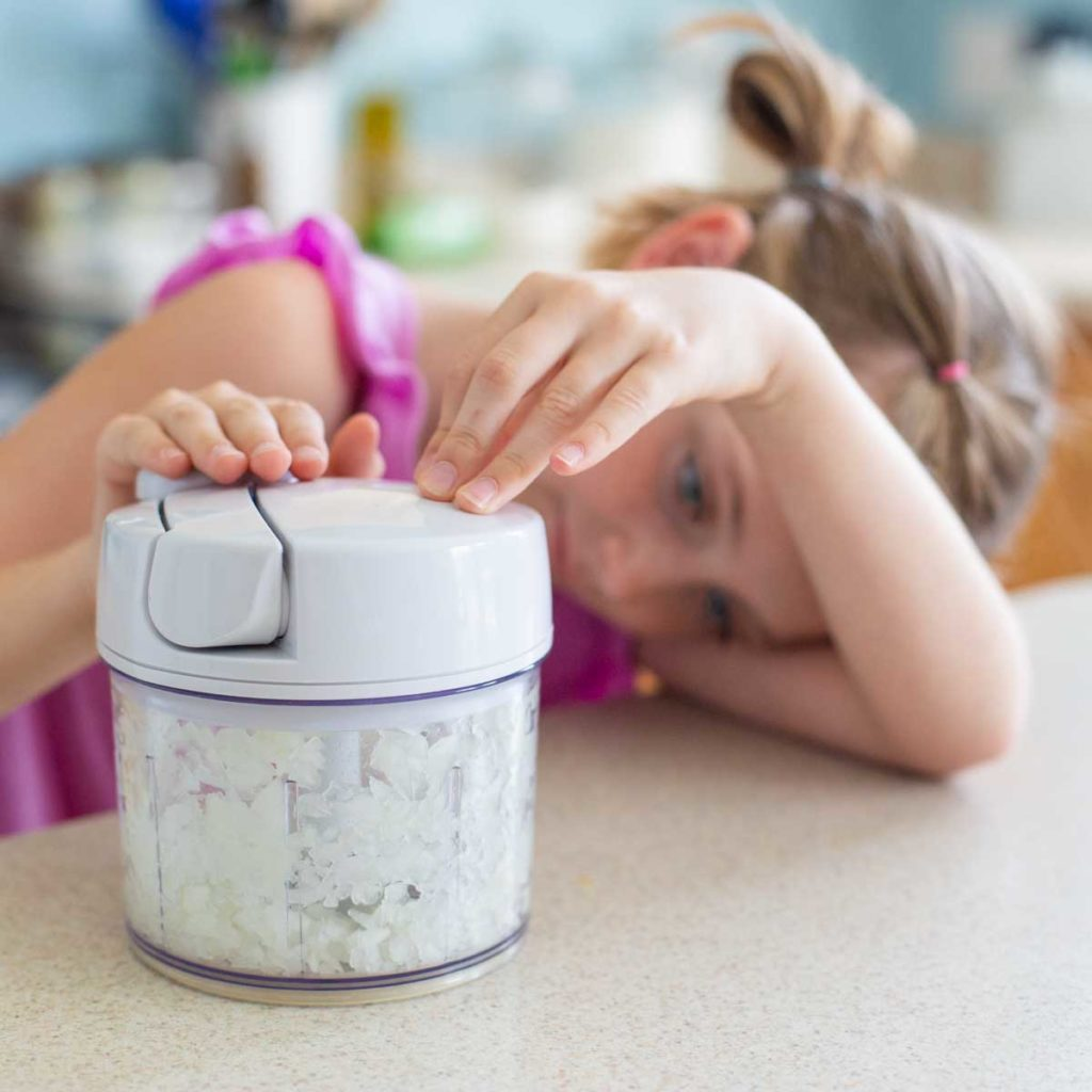 A young girl chops onions in a food processor.