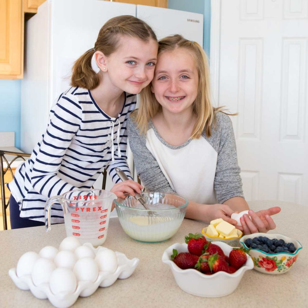 Two girls cooking in the kitchen.