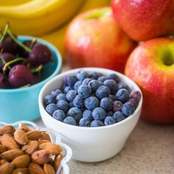 A bowl of fresh blueberries sits next to a bowl of cherries, a pile of red apples, fresh bananas, and a bowl of whole almonds.