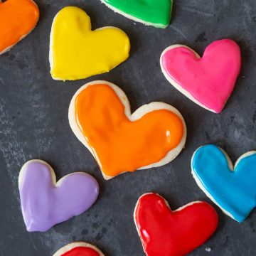 Heart-shaped frosted sugar cookies in rainbow colors against a black chalkboard.