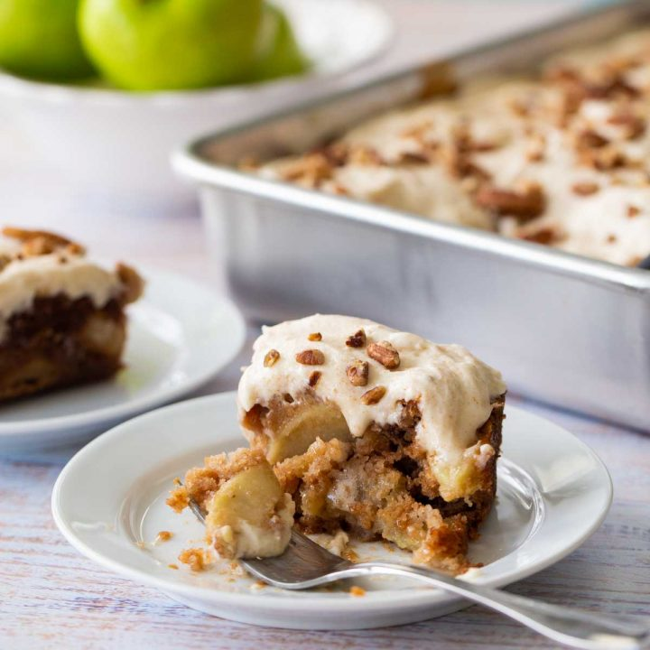 A square slice of apple cake topped with soft frosting and pecans sits in front of the metal baking pan it came from. A bite is missing.