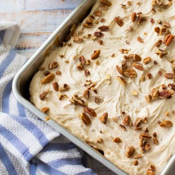 A metal baking pan filled with a sheet cake topped with browned butter frosting and chopped pecans.
