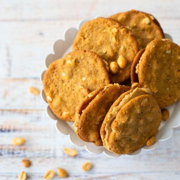A platter of crunchy peanut butter sandwich cookies next to a scattering of peanuts.