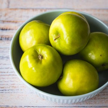 A bowl full of Granny Smith apples sits on a table.