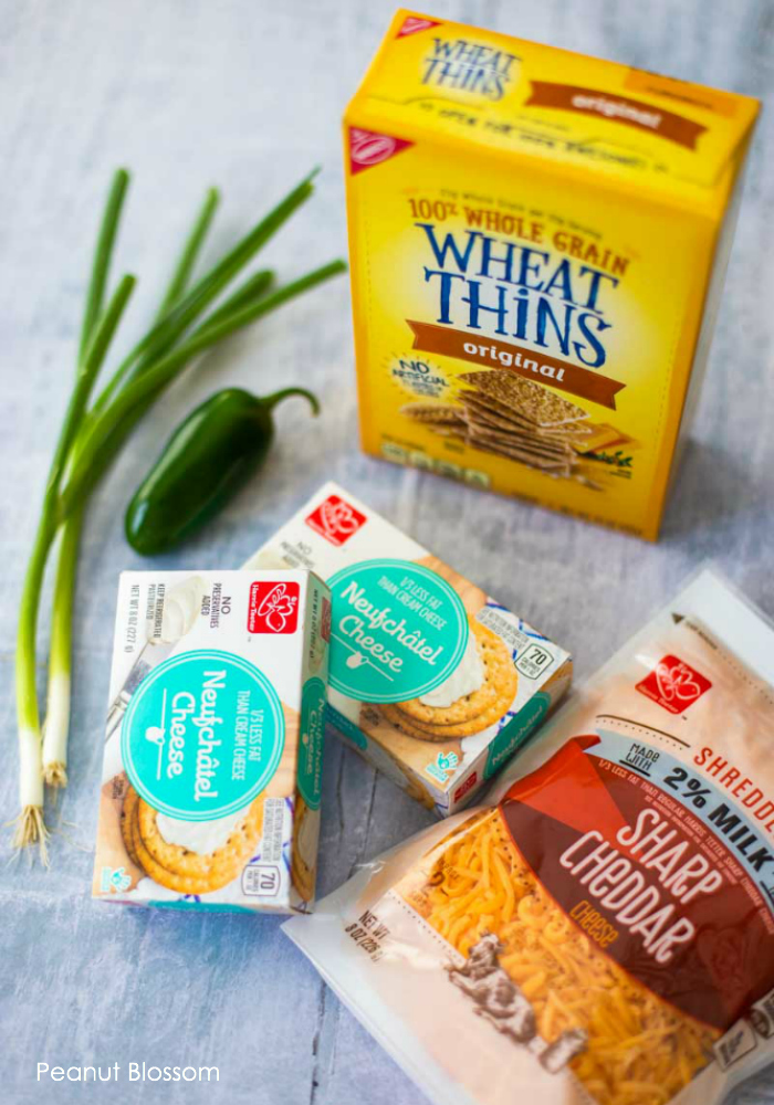 The easy jalapeno cheese ball requires just a few easy ingredients: Wheat Thins, 2 green onions, a jalapeno pepper, 2 packages of Neufchatel Cheese, and some shredded sharp cheddar.