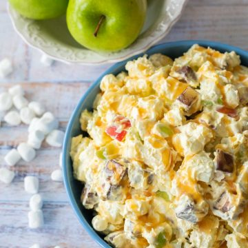 A bowl of creamy Snicker salad has apples, marshmallows, Snickers tossed together.