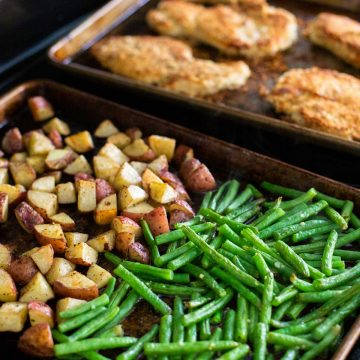 Two sheet pans hold roasted green beans, roasted potatoes, and a breaded sheet pan chicken cutlet.
