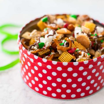 A red polka dot container has Christmas Chex Mix with red and green sprinkles over the top.