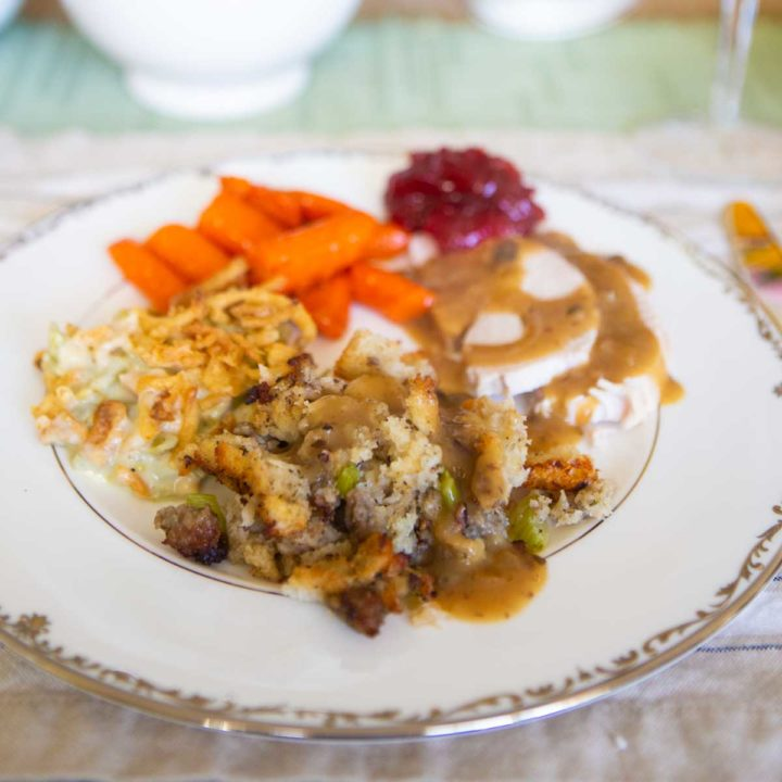 A full plate of Thanksgiving dishes drizzled with homemade gravy.