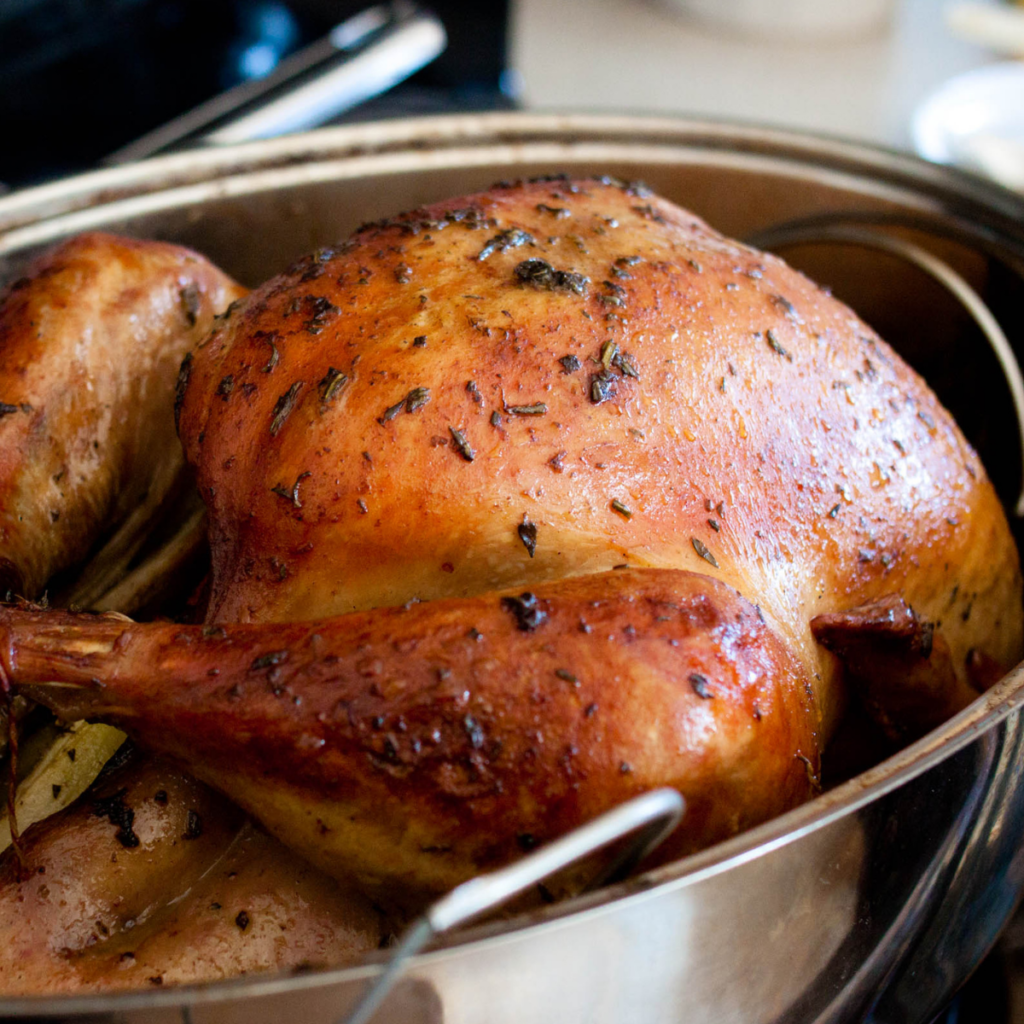A roasted turkey sits in a metal roasting pan, golden brown all over.