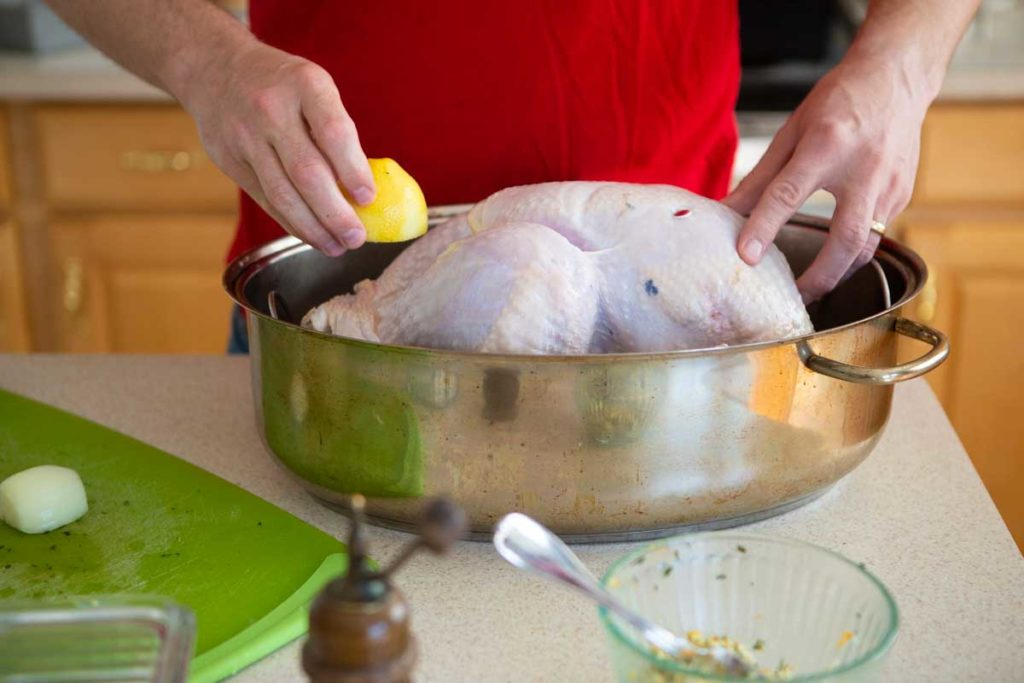 Hands are stuffing fresh lemon inside the turkey in a roasting pan.