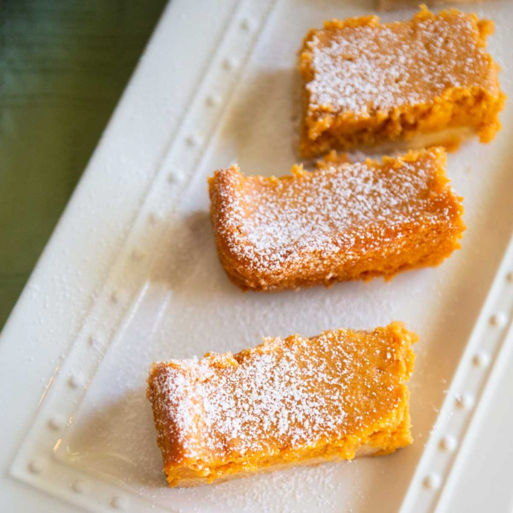 Slices of homemade pumpkin gooey butter cakes are dusted with powdered sugar on a white platter.