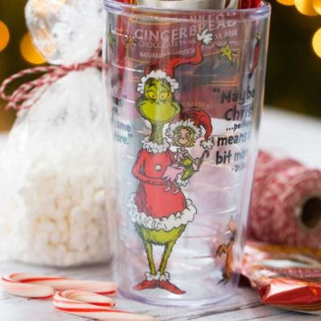 A Grinch tumbler with a bag of marshmallows and mini candy canes.