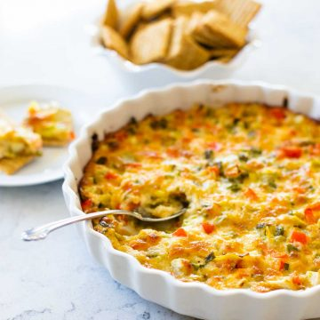 A dish of baked artichoke dip shows diced red peppers and green onions. There's a serving spoon taking a scoop. A bowl of crackers sits in the back.