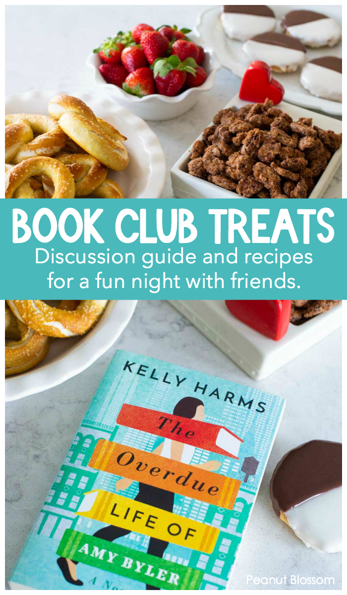 Book Club Treats on display include pretzels, strawberries, candied nuts, and black and white cookies next to the book of the month: The Overdue Life of Amy Byler