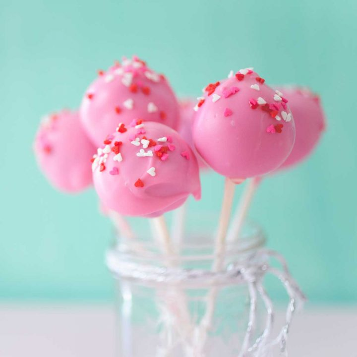 A mason jar filled with pink brownie pops on white sticks with red and white sprinkles.