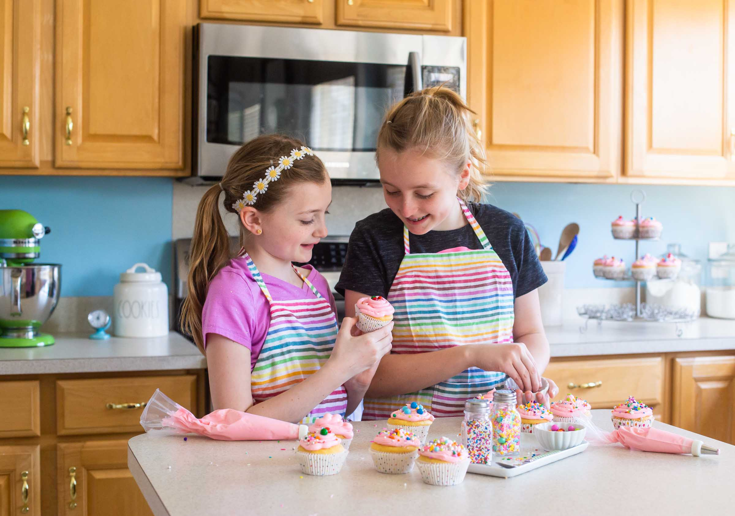 My two girls baking pink-frosted cupcakes in our kitchen as we test The Ultimate Kids' Baking Book recipes.