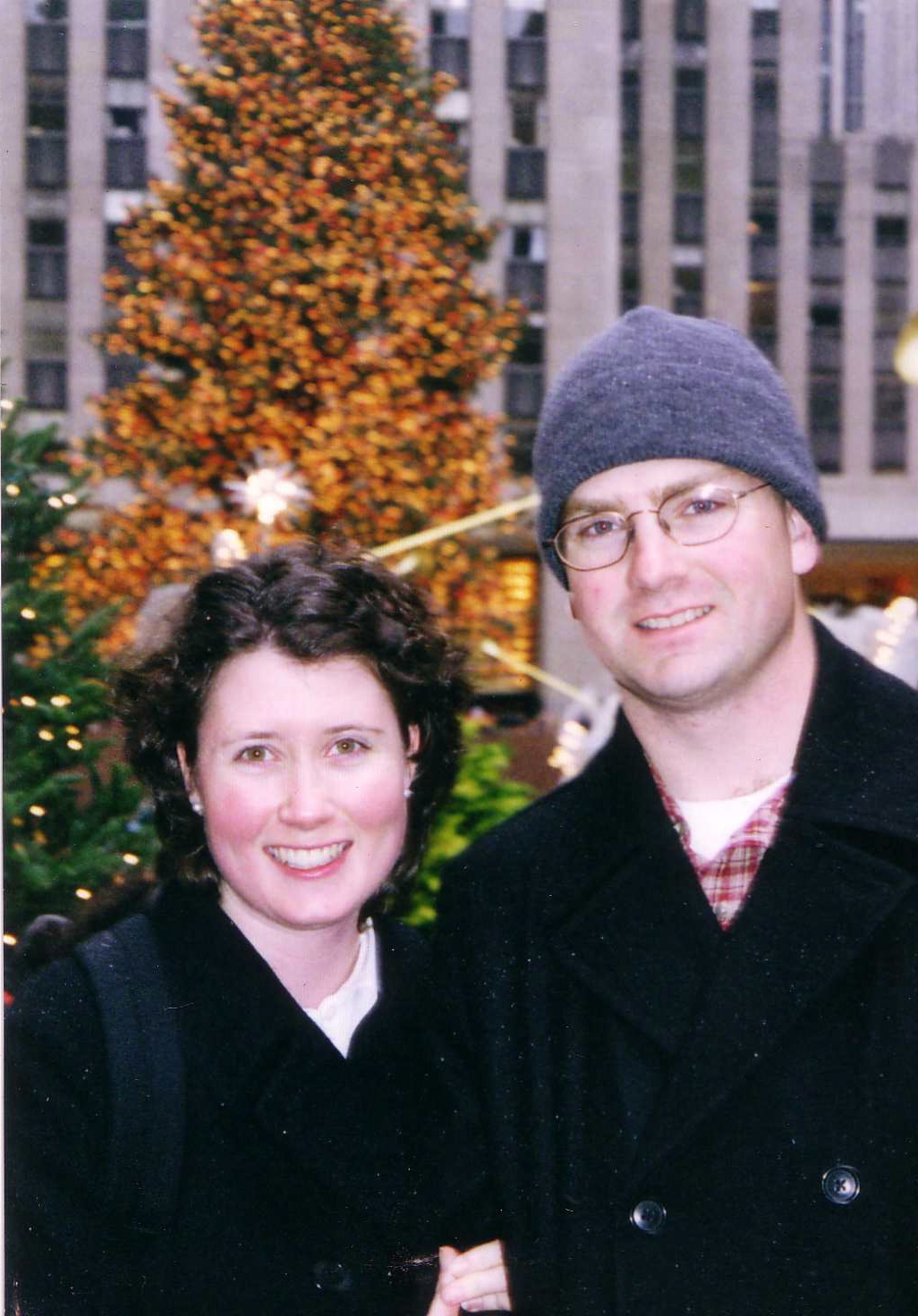 A young couple in front of the Rockefeller Center Christmas tree