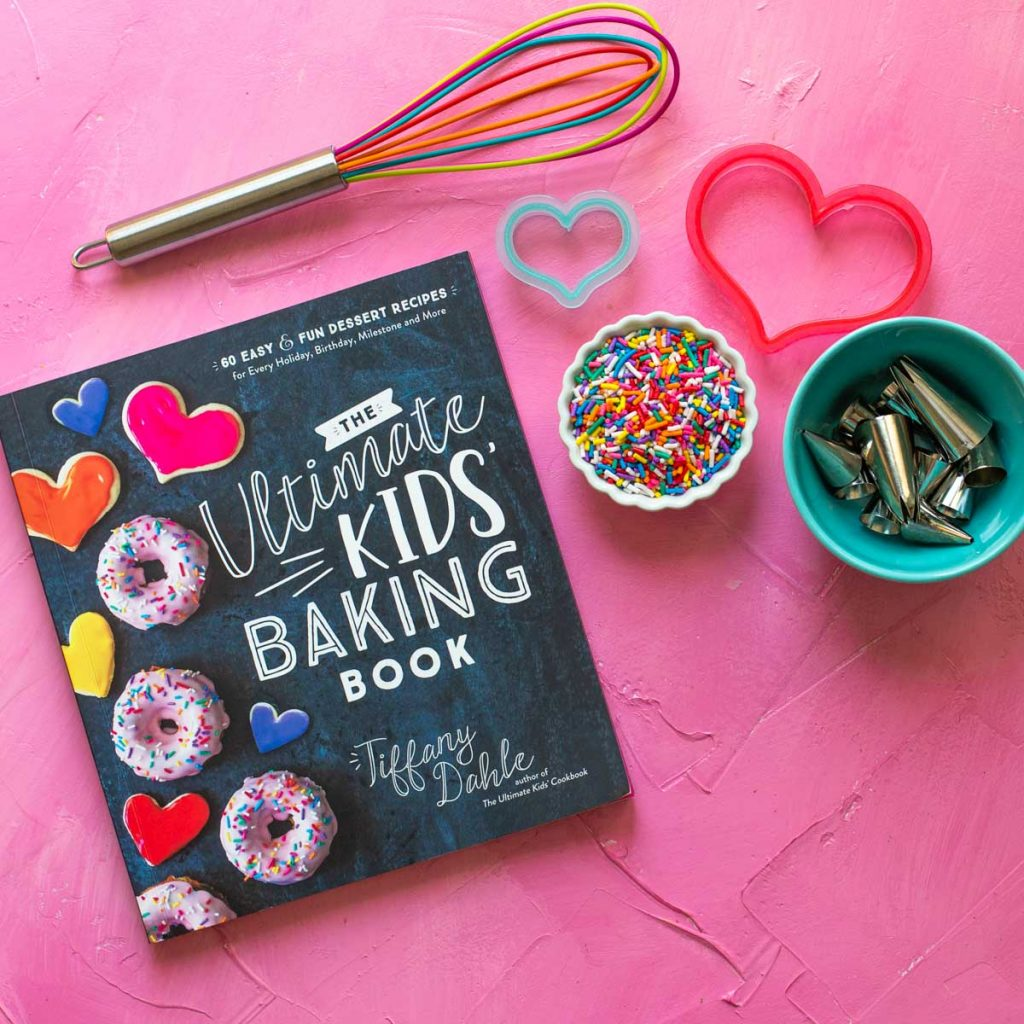 A copy of The Ultimate Kids' Baking Book sits on a pink background with a whisk, sprinkles, and cookie cutters.