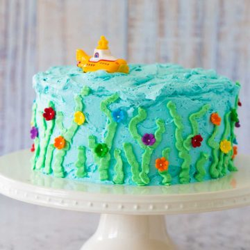 A light blue birthday cake has been decorated to look like an under the sea garden and has a yellow submarine on top.