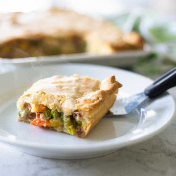 A slice of ham slab pot pie sits on a plate with a serving spatula. Big chunks of fresh veggies peek out from under a flaky pie crust.