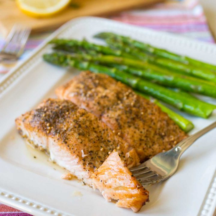 A platter of oven baked salmon next to roasted asparagus has a fork showing the flaky pink fish.