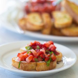 2 crostini toasts are topped with diced strawberries and a sprinkle of fresh basil to show the strawberry bruschetta appetizer. A plate of crostini sits in the background.