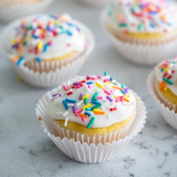 A vanilla cupcake in a white wrapper has white vanilla glaze and rainbow sprinkles on top. More cupcakes are in the background.
