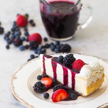 A slice of plain cheesecake has fresh strawberries, blackberries, and blueberries sprinkled over the top and on the table. A drizzle of dark purple triple berry sauce is dripping down from the top. A pitcher of sauce is nearby.