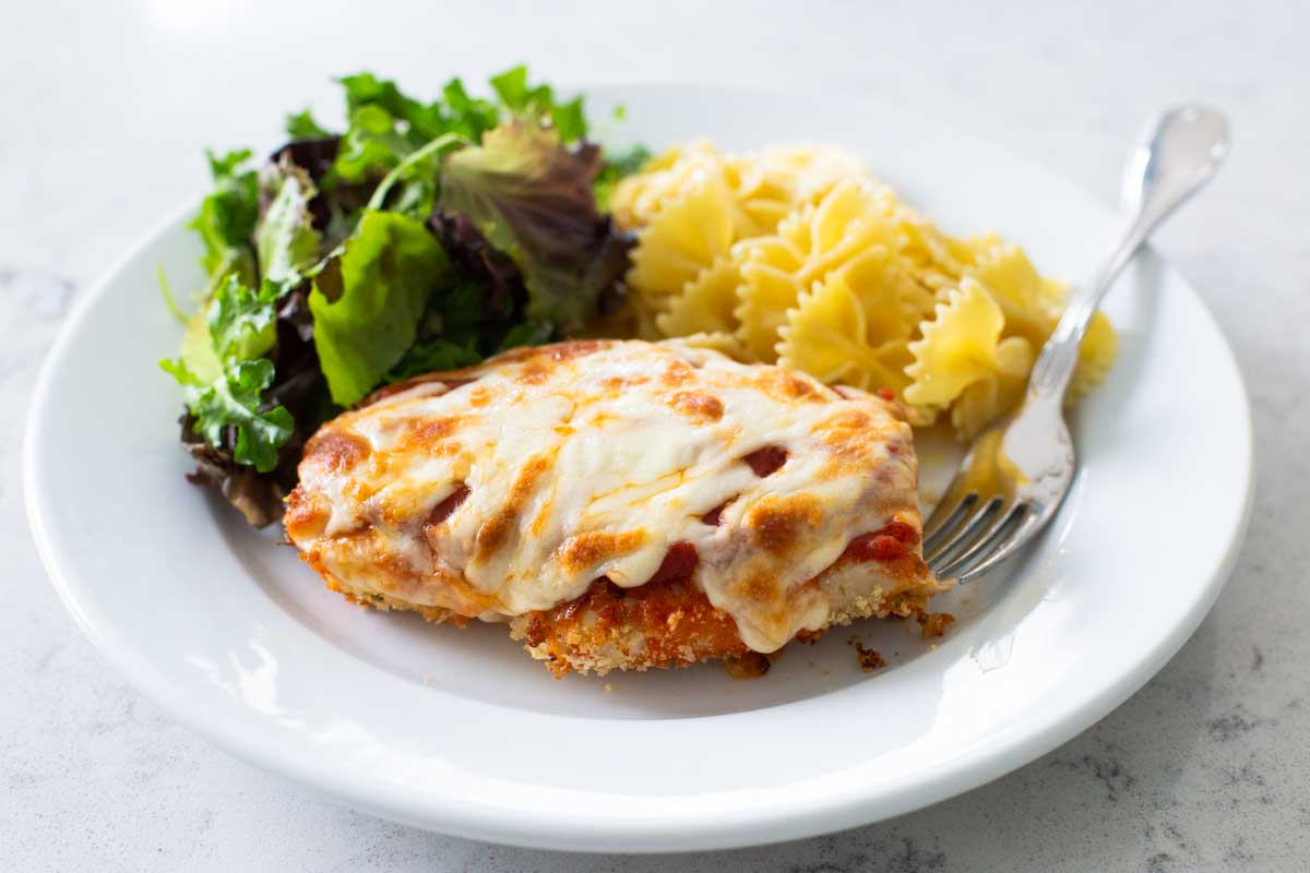 Baked chicken parmesan on a white plate with a side of fresh salad greens and buttered bowtie pasta.